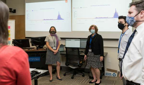 Dr. Cindy Prins (right) and Jerne Shapiro (left), the lead epidemiologist for UF Health Screen, Test & Protect, meet with other members of the Screen, Text & Protect team. Photo by Louis Brems.