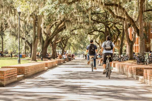 Student bicycling through campus